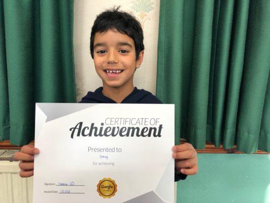 Devaj happily holding his Silver reward at Genie Tutors Harborne! Well done!